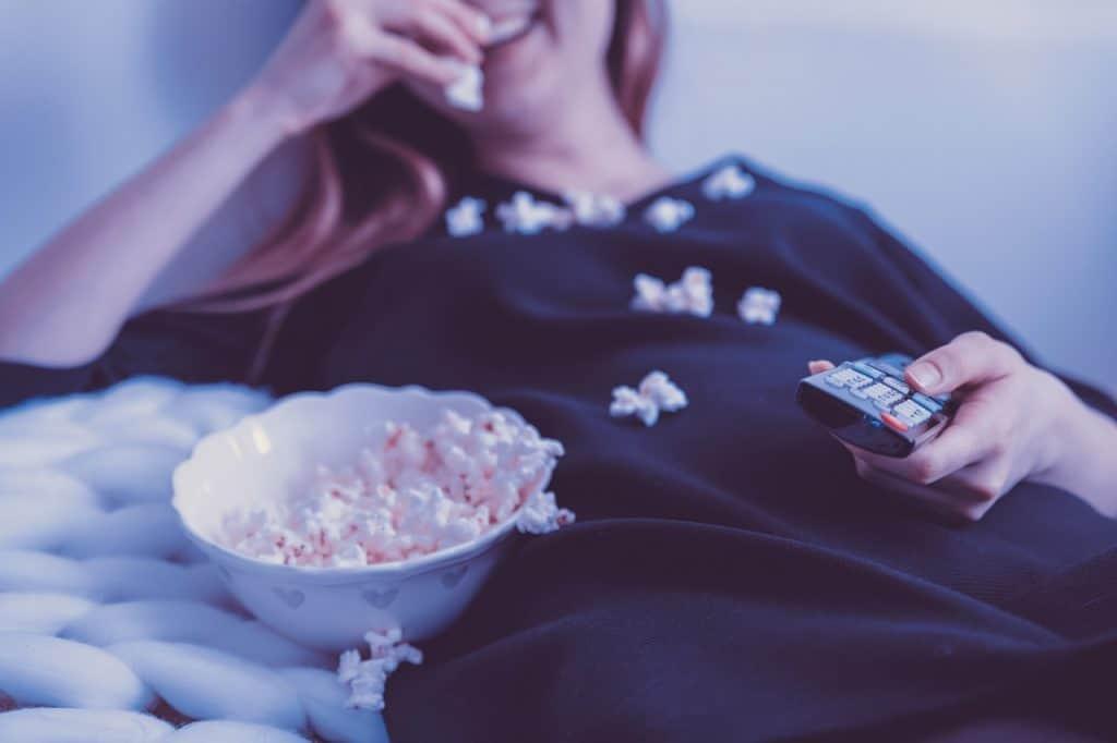 mulher assistindo tv com controle na mão e pipoca no colo