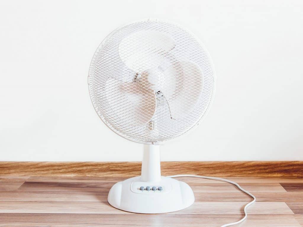 Na foto um ventilador de mesa branco.