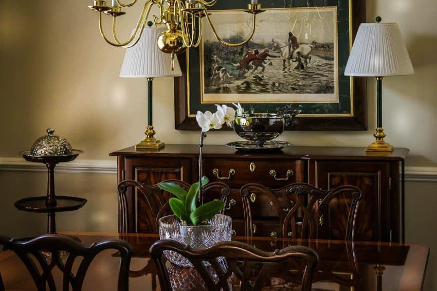 Sala de estar com decoração clássica e rústica. Há uma mesa de madeira com 4 cadeiras e um aparador de madeira com dois abajures e um utensílio decorativo. Acima dele, há um quadro pendurado na parede.