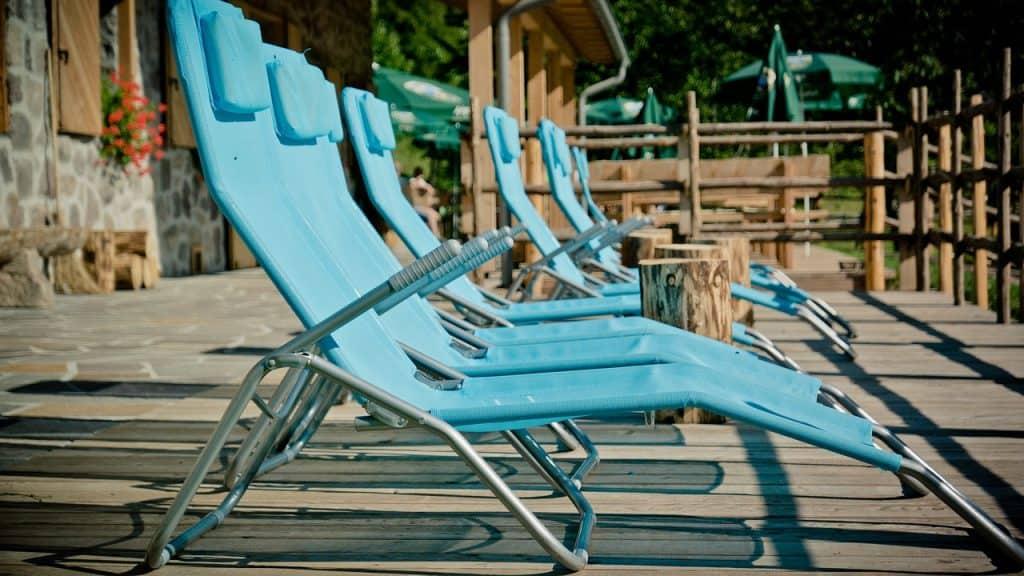 Imagem de espreguiçadeiras verdes posicionadas em fila em um deck.