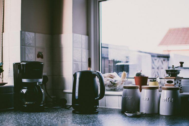 Imagem de chaleira elétrica preta ao lado de cafeteira e outros eletroportáteis em bancada de cozinha