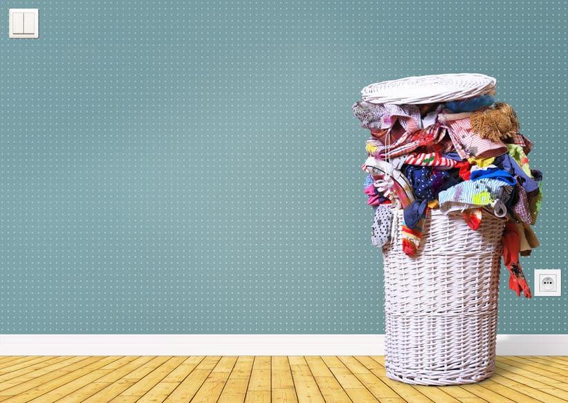Imagem mostra cesto de vime cheio de roupas.