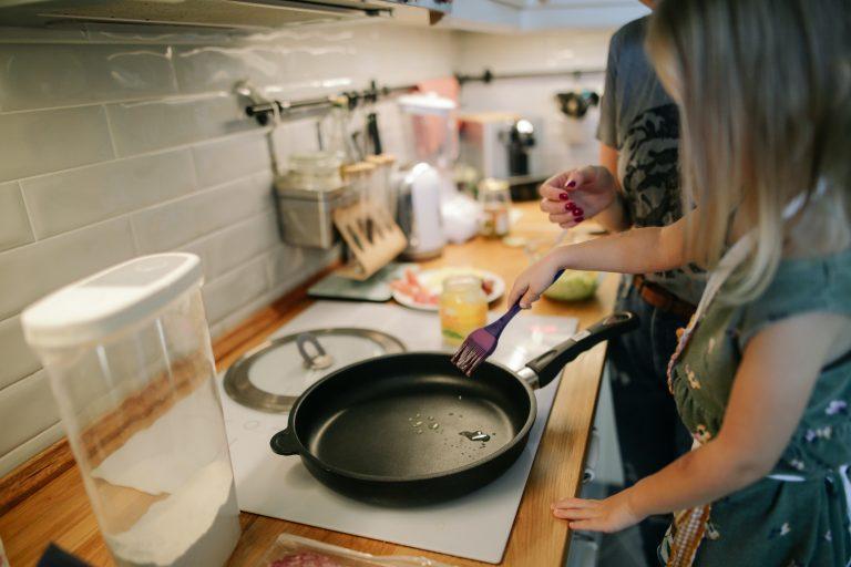 Imagem de uma mulher preparando um alimento numa frigideira antiaderente.