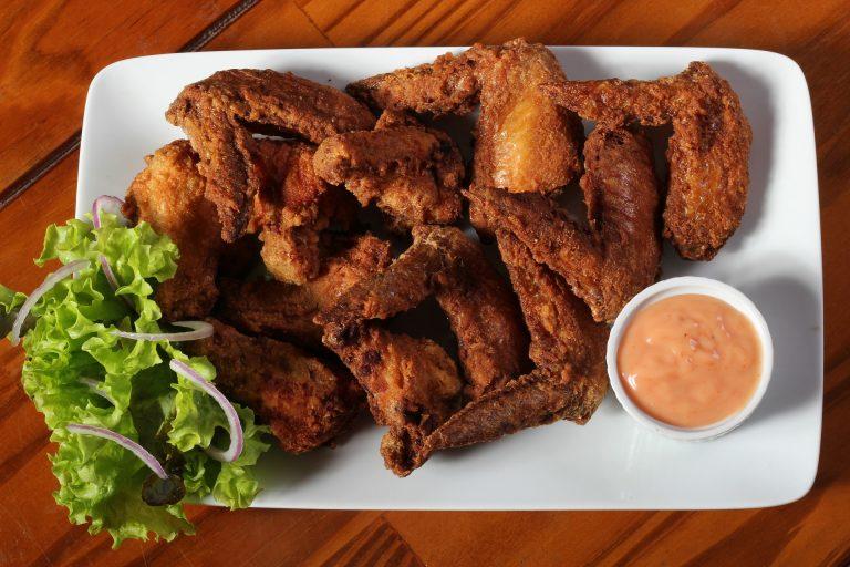 Imagem de salada e asinhas de galinha fritas em petisqueira branca com molho servido ao lado