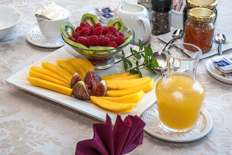 Na foto uma mesa posta com suco, geleias, frutas e outros itens.