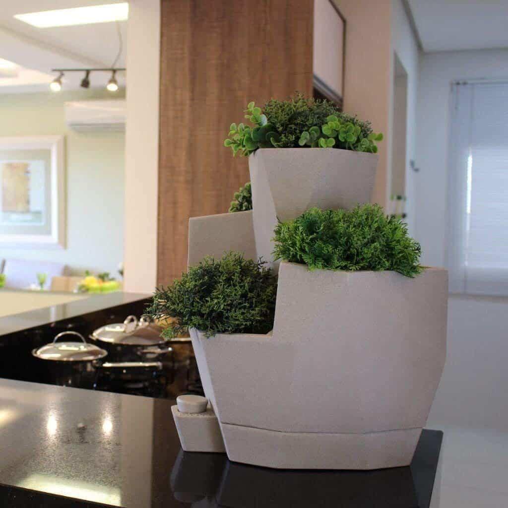 Lindo vaso autoirrigável em uma bancada de cozinha.