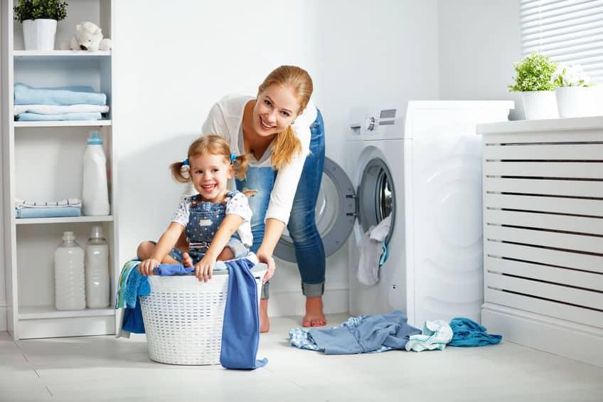 Imagem de mãe e filha com cesto de roupas de plástico.