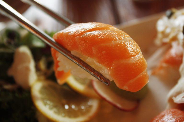 Foto de um hashi segurando um tradicional tipo de sushi, o niguiri. Ao fundo, outros alimentos.
