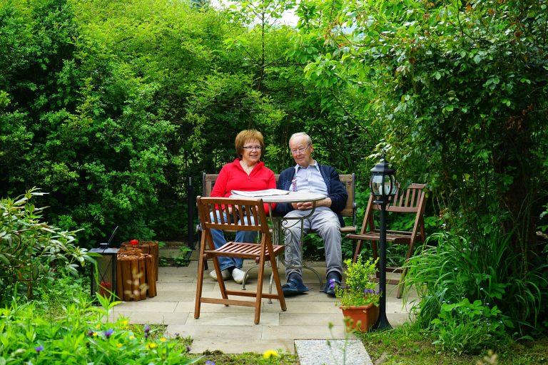 Casal de idosos juntos em um banco de conjunto no jardim