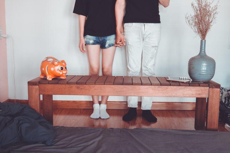Foto que mostra da metade do corpo pra baixo de um casal de mãos dadas, encontado na parede, de frente para uma banqueta, com um cofrinho e um vaso em cima.