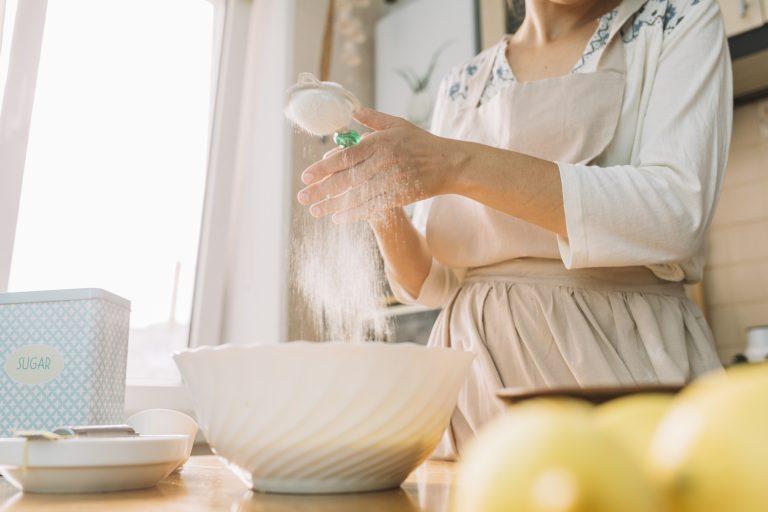 Mulher peneira ingrediente seco direto em tigela para preparo de receita