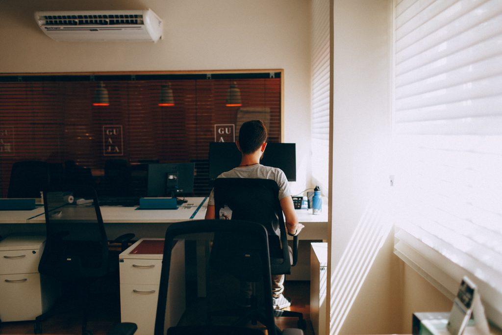 Homem sentando em mesa de trabalho com ar condicionado na parede.