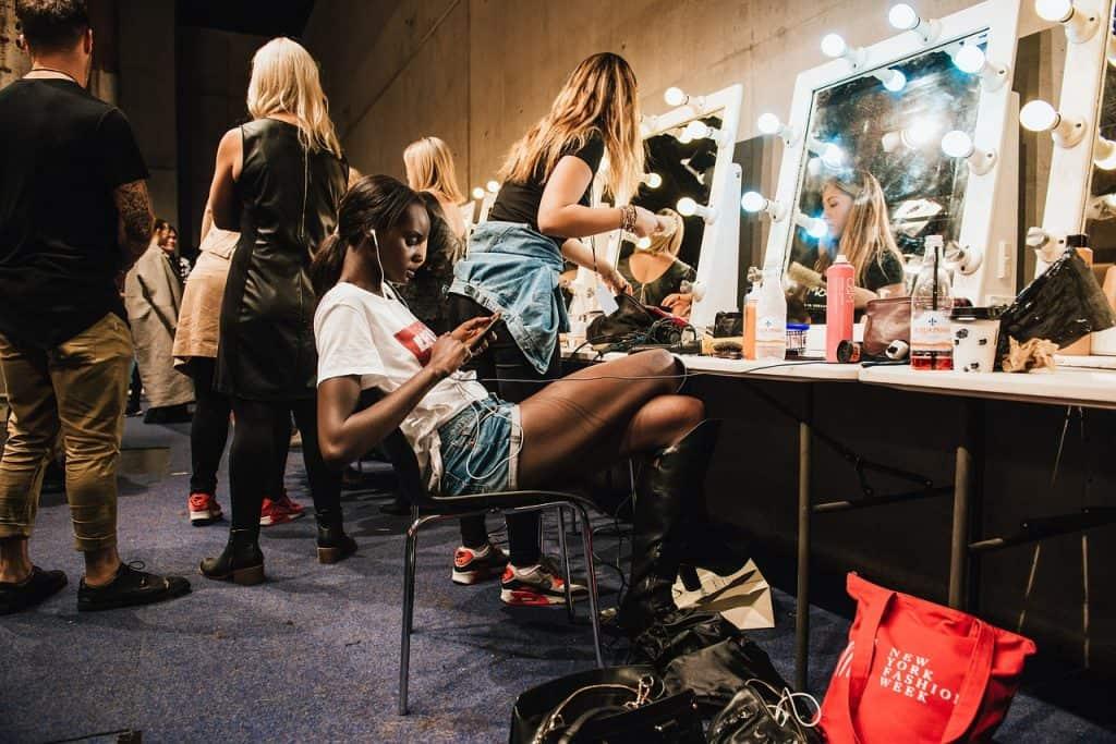 Imagem de mulheres de maquiando em penteadeira iluminada.