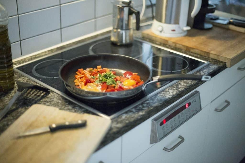 Panela com vegetais cozinhando sobre o cooktop.
