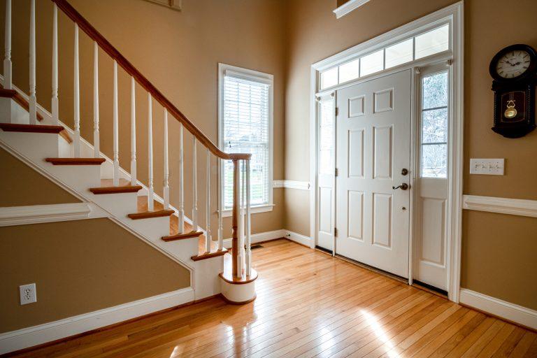 Entrada interna de uma casa com escada e interruptores de luz na parede.