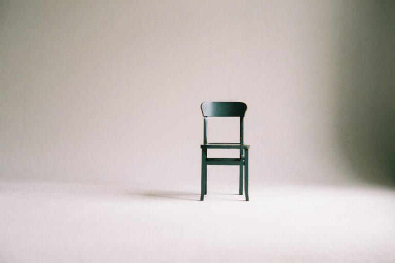 Foto de uma cadeira preta, simples, em um espaço com parede e chão branco.