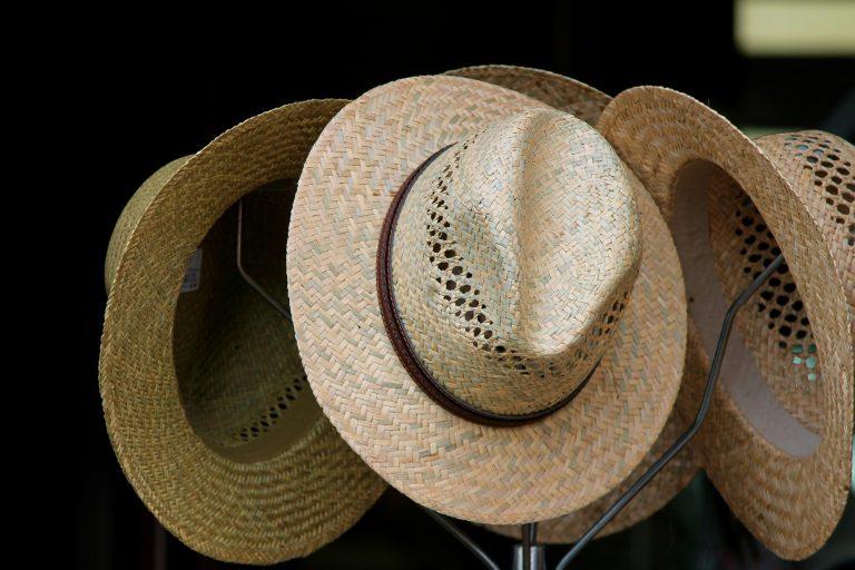 Foto da parte superior de um cabideiro de chão, com quatro chapéus de palha pendurados em seus ganchos.
