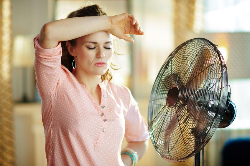 Moça se refresca em frente a ventilador com pedestal