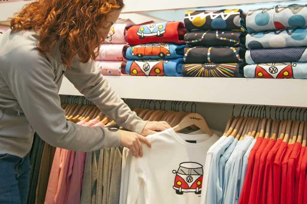 Uma mulher segurando uma camiseta que tem cabide de madeira em uma seção de uma loja de departamentos.