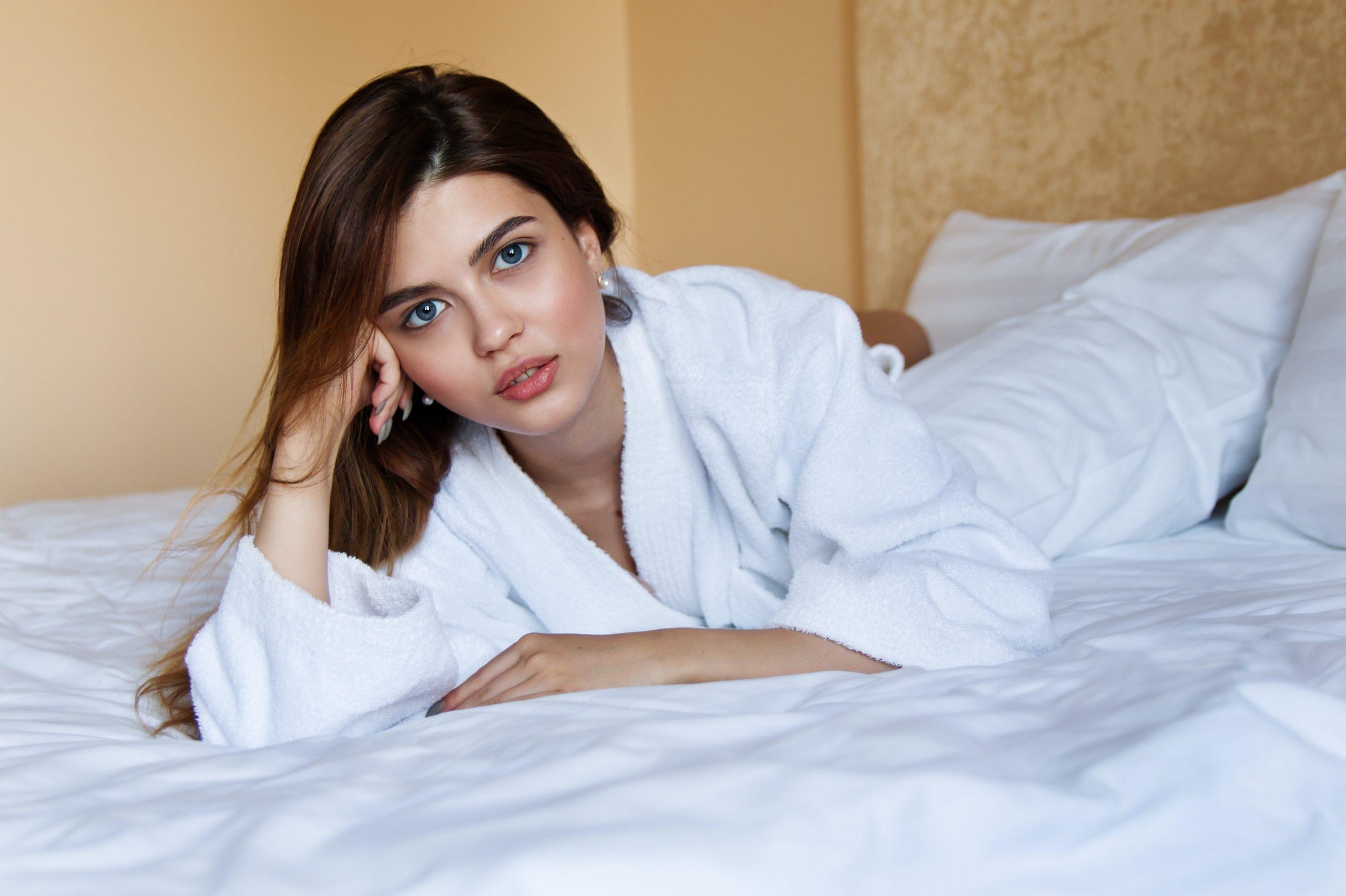 Imagem de uma mulher deitada em uma cama.