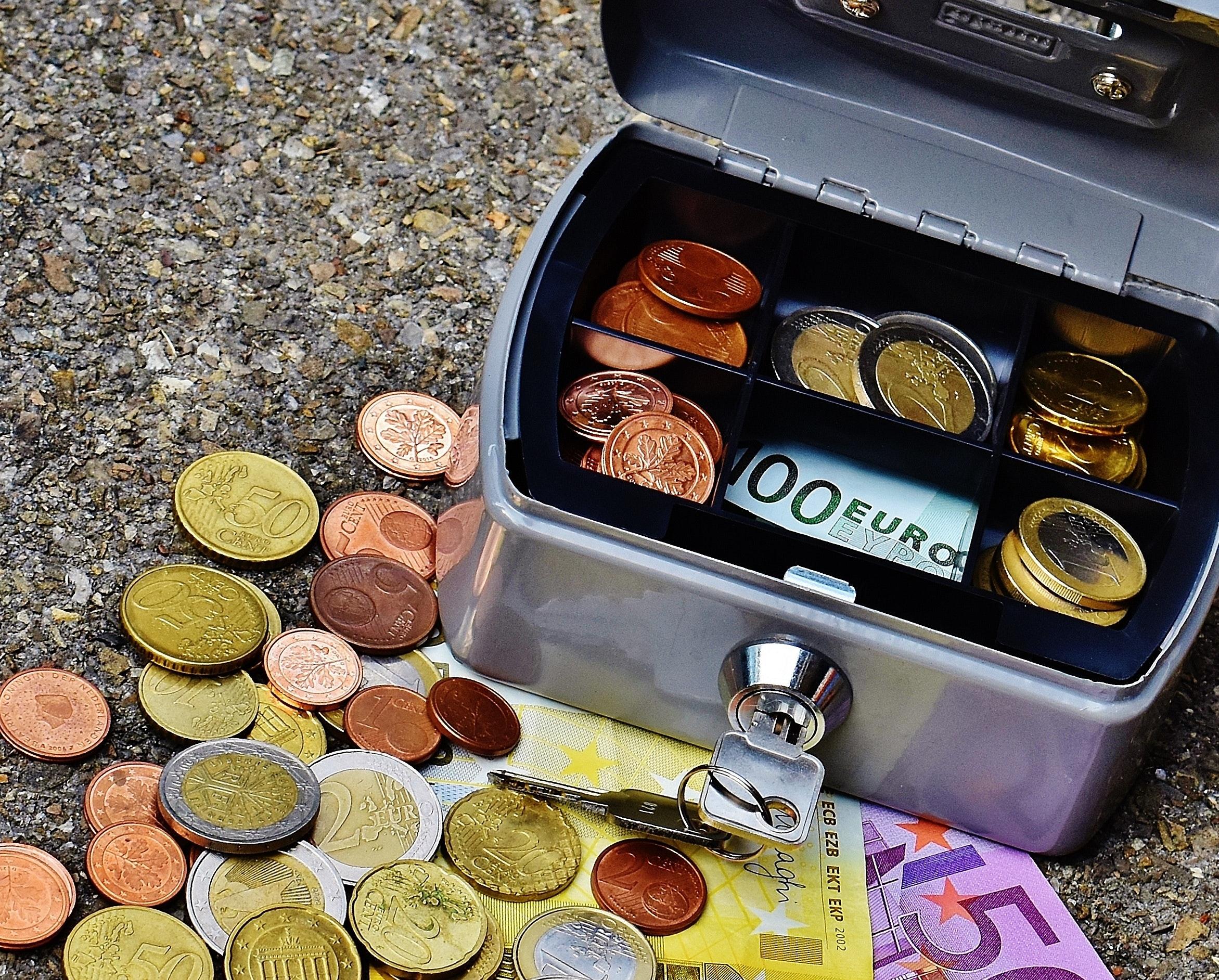 Imagem mostra um porta-valor aberto, com a chave na fechadura e notas e moedas e seu interior. Ele está sob uma superfície áspera e sob notas e moedas espalhadas.