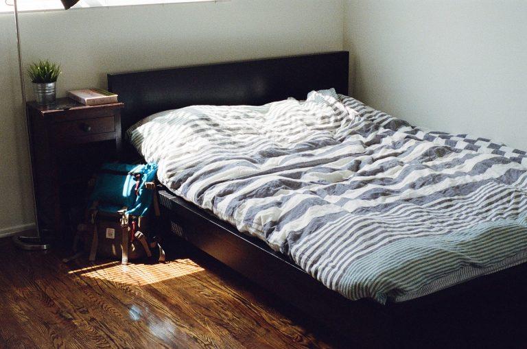 Imagem de quarto com cama coberta por edredom queen com mochila de viagem ao lado