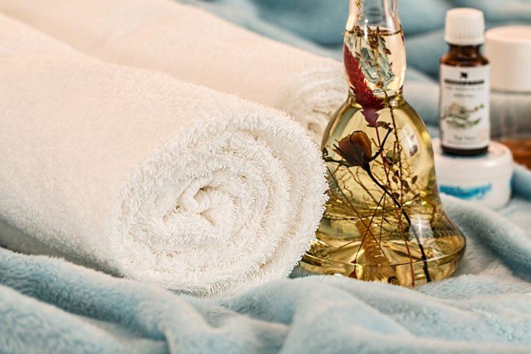 Imagem de aromatizante de ambientes em embalagem de vidro com flores desidratadas e conjunto de toalhas