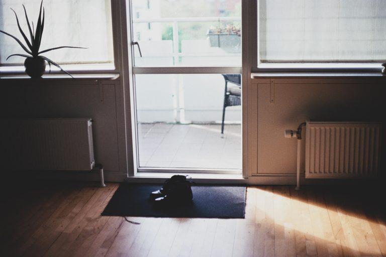 Imagem de sapato sobre capacho preto em área interna junto de uma porta de vidro