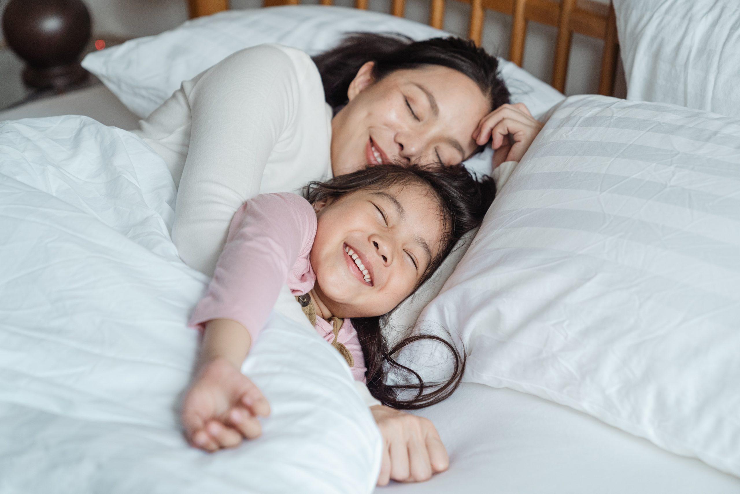 Imagem de mãe e filha deitadas.