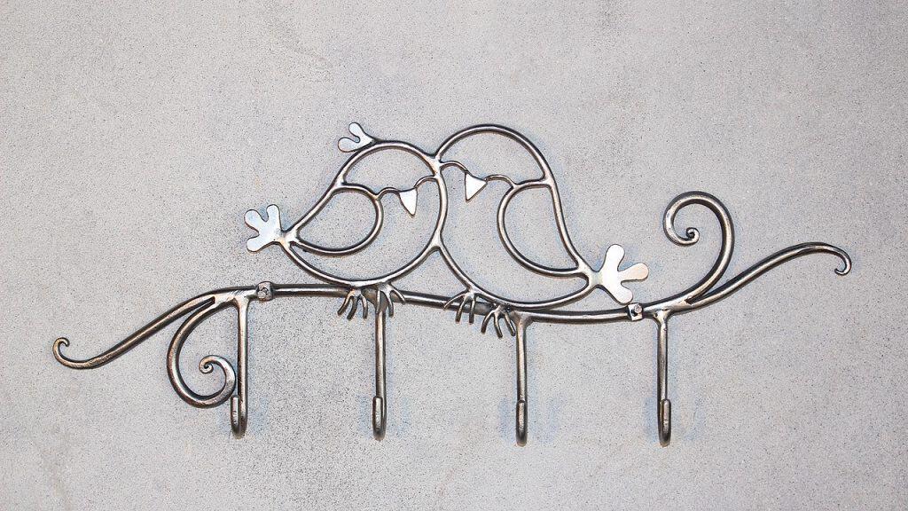 Um chaveiro cromado personalizado na forma de dois pássaros e um galho.
