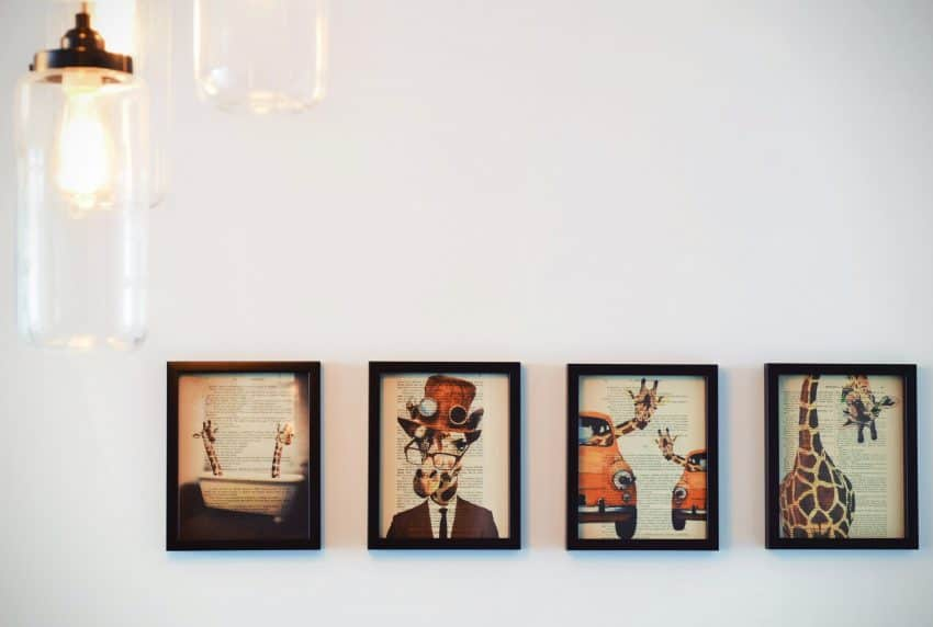 Foto de uma parede branca, com quatro quadros com a temática girafa, dispostos um ao lado do outro. Na frente, um conjunto de lâmpadas com estilo mais descolado.