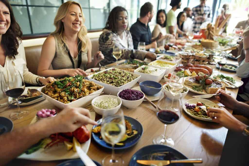 Grande mesa com familiares almoçando e rindo.
