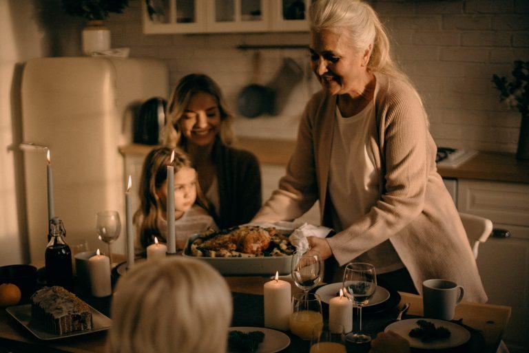 Na foto uma mulher servindo um frango assado para pessoas ao redor de uma mesa.