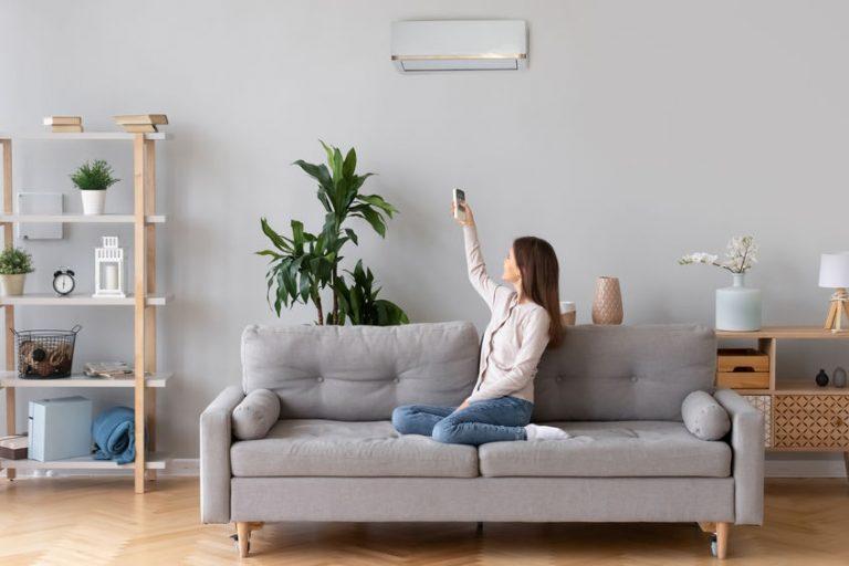 Mulher no sofá, ligando o ar condicionado com controle remoto.