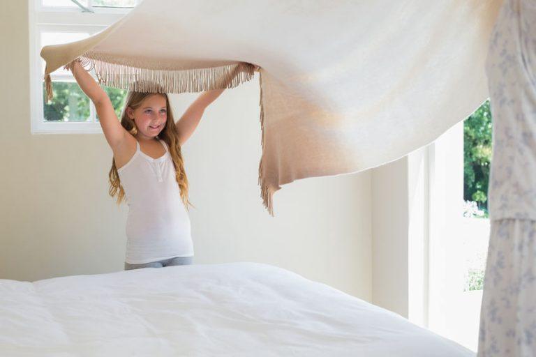Menina ajuda adulto a arrumar a cama