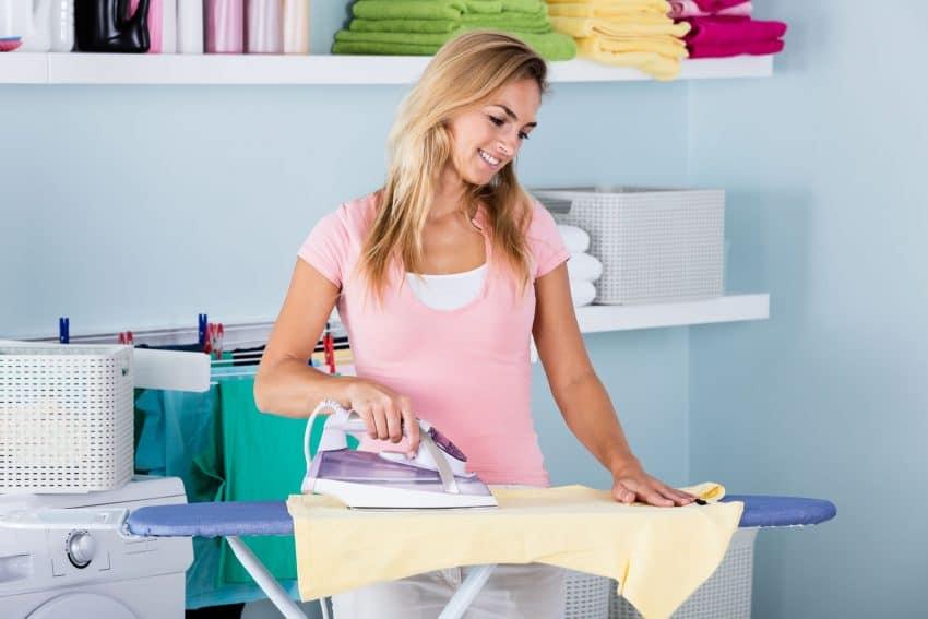 Mulher passando roupa.