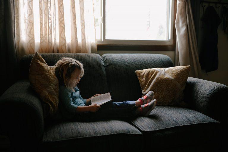 Imagem de criança lendo sentada em sofá de dois lugares com almofadas