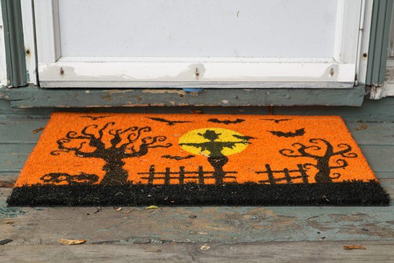Imagem de capacho com estampa de dia das bruxas junto de porta de madeira