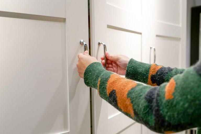 Foto de uma mão abrindo o gaveteiro de um armário de cozinha cinza.