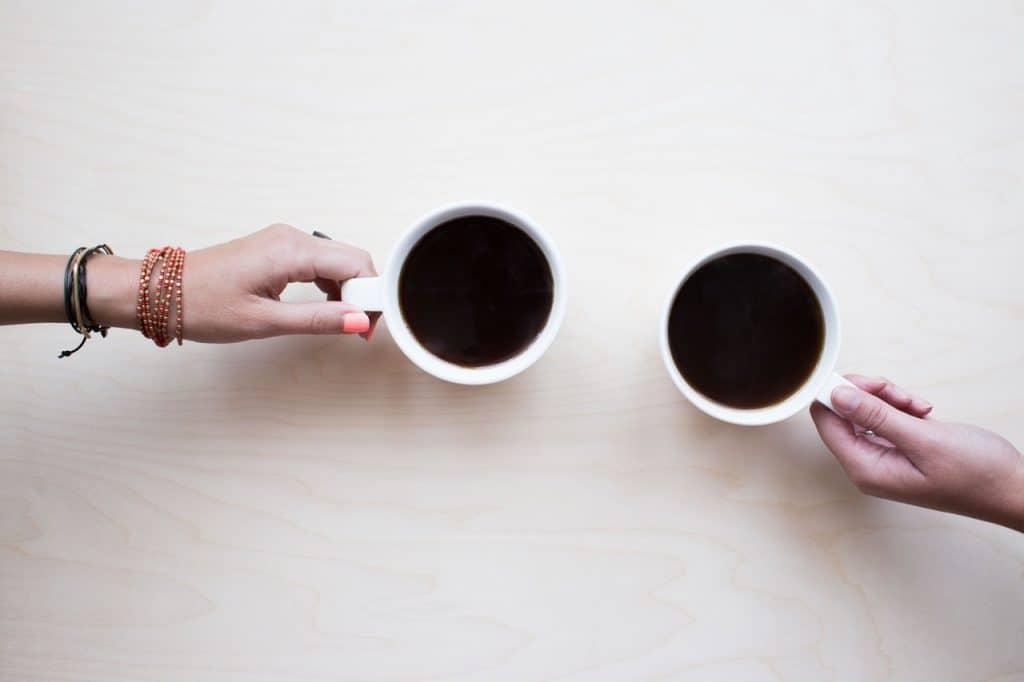 Imagem de duas xícaras de café preto sendo seguradas.