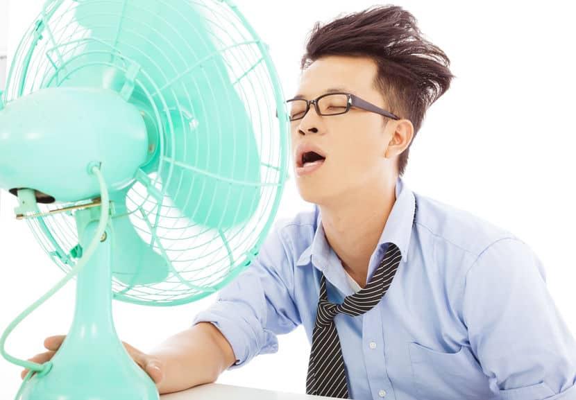 Homem se refrescando com ventilador no trabalho.