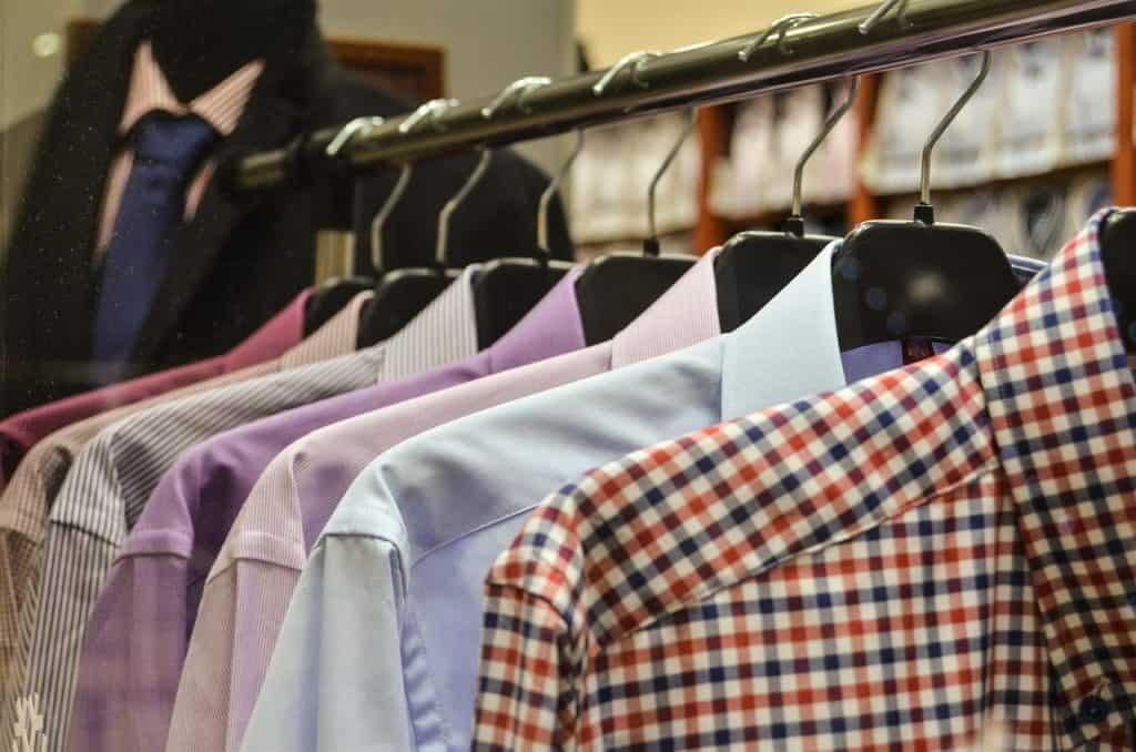 Camisas de botão penduradas com cabides em uma arara de ferro.