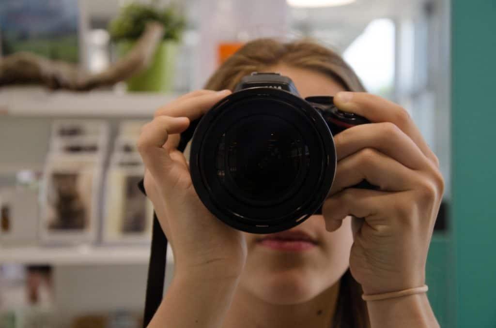 Imagem de mulher segurando uma câmera fotográfica digital
