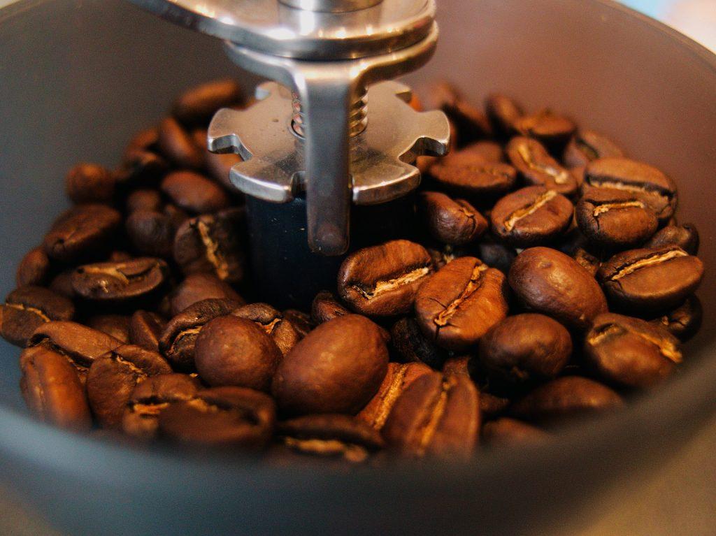 Imagem do interior de um moedor de café manual com grãos
