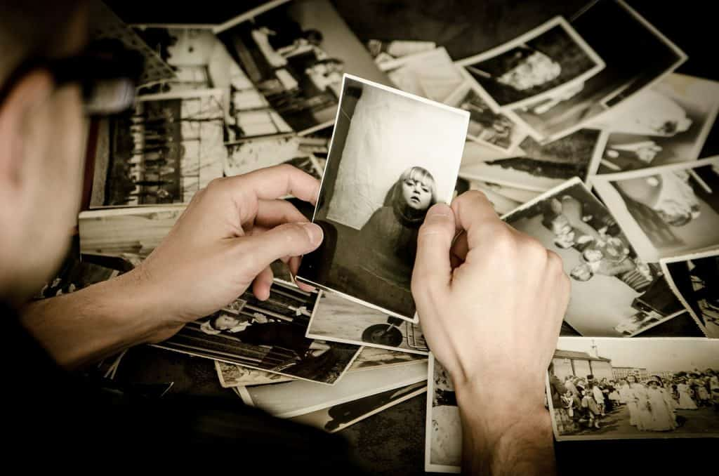 Imagem de pessoa segurando uma foto antiga e desbotada