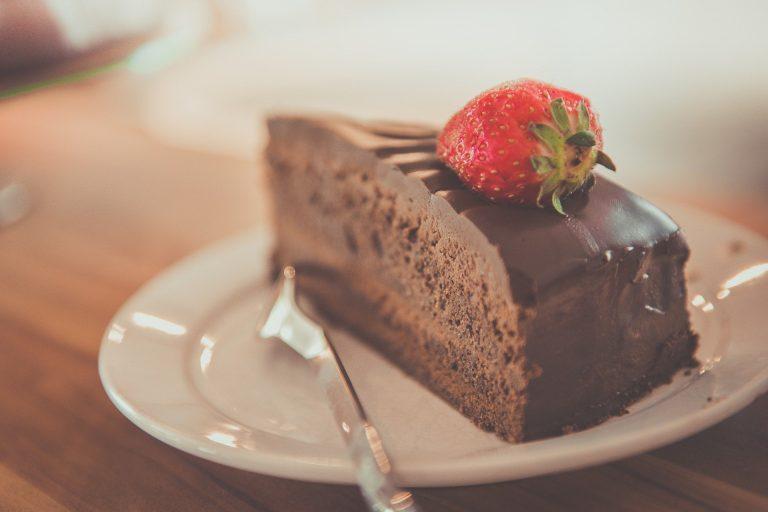 Imagem de bolo de chocolate com morango no topo servido em prato branco