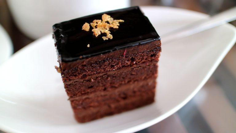 Imagem de bolo de chocolate com cobertura servido em prato branco
