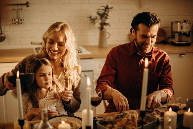 Na foto três pessoas sentadas em frente a uma mesa de jantar com velas acesas.