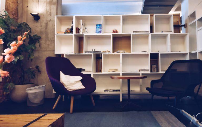 Foto de um espaço de uma sala. Uma estante branca ao fundo, com suas poltronas na frente, acompanhadas de uma mesinha redonda de centro. Ao lado, uma planta.