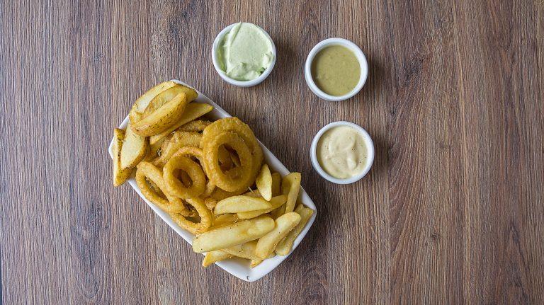 Imagem de batatas fritas e anéis de cebola em petisqueira branca com três potes de molho sobre mesa de madeira